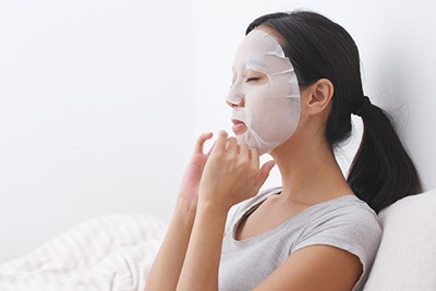 women with sheet mask on