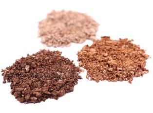 Three piles of crushed makeup containing ingredients you should avoid