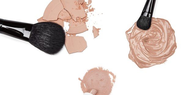 Makeup brushes laying next to piles of the best foundations