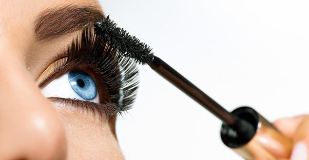 Close up of blued woman applying mascara to her lashes after extending the life of her mascara.
