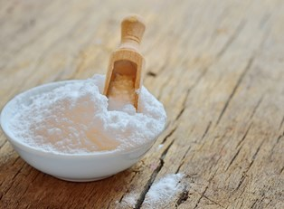 Bowl of baking soda with a wooden scoop standing in it.