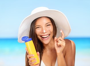 a woman puts sunscreen on her nose while at the beach