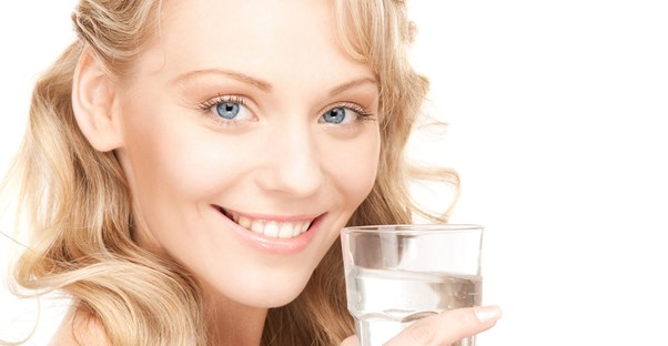 Young woman smiles as she drinks water and improves her skin health.