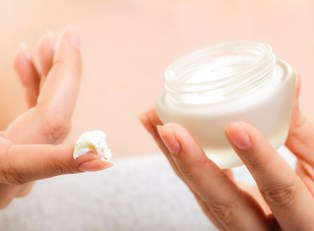 A woman scoops moisturizer out of a jar to apply to her oily skin.