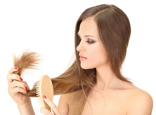 Young woman examining her split ends and wondering if there's a natural hair treatment for them
