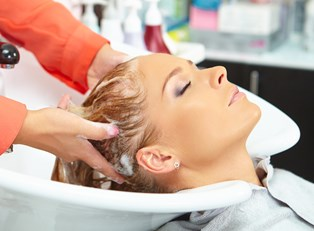 Woman having her hair washed with anti-frizz shampoo