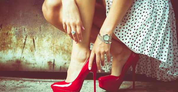 Woman putting on red pumps to pull together an outfit