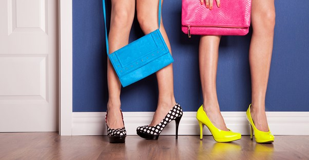 Two girls in stilettos holding their fully stocked purses.