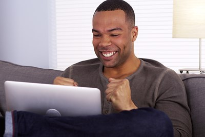 Excited man looking at laptop