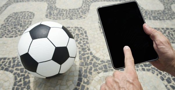 Man with soccer ball and computer tablet