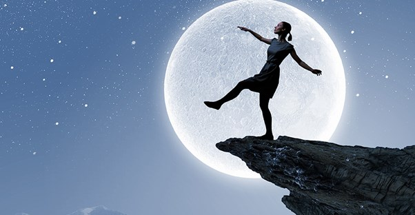 Woman with the moon behind her about to step off a cliff
