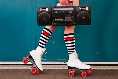 Woman wearing white roller skates with red wheels carrying a boombox