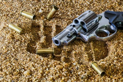 gun in sand next to footprint