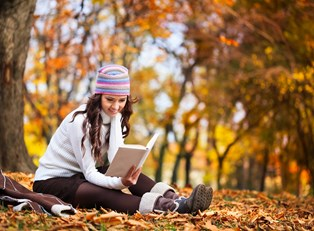 Young woman reading a book outside in the fall weather