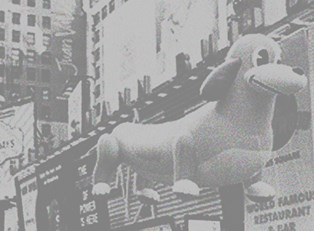 A black and white image of a dog shaped helium balloon in the Macy's Thanksgiving Day Parade.