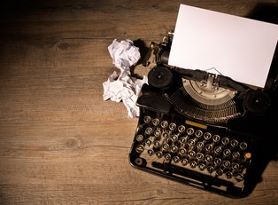 Typewriter with crumpled pieces of paper lying beside it