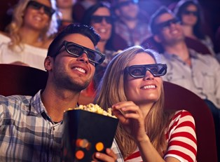 A couple shares popcorn while watching a 3D movie