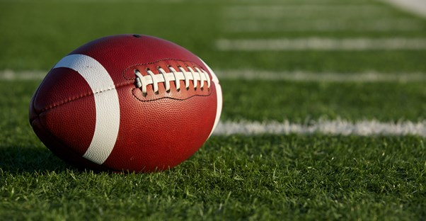 A football laying on a football field.