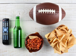 Items sitting on a table at a super bowl party.
