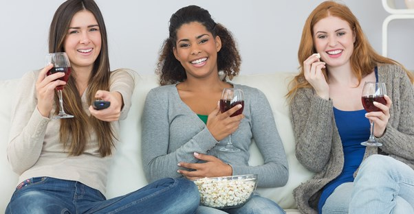 Three girls watch Scandal while eating popcorn and drinking red wine