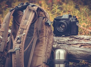 A backpack and camera taken on a camping trip.