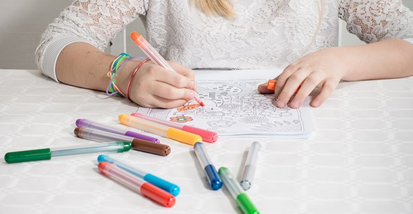 Girl coloring on coloring sheet