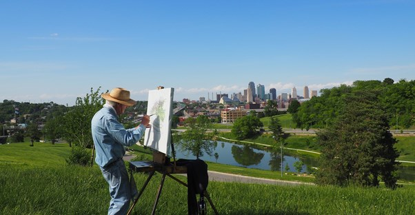 a retired man painting a landscape in front of a city skyline