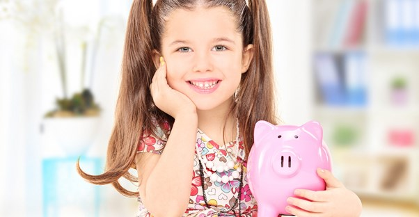 a young holds a pink piggy bank filled with her allowance money