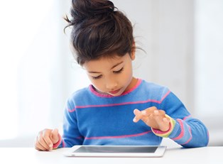 a young girl plays with apps on her tablet
