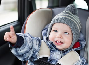 a toddler enjoys riding in his car seat