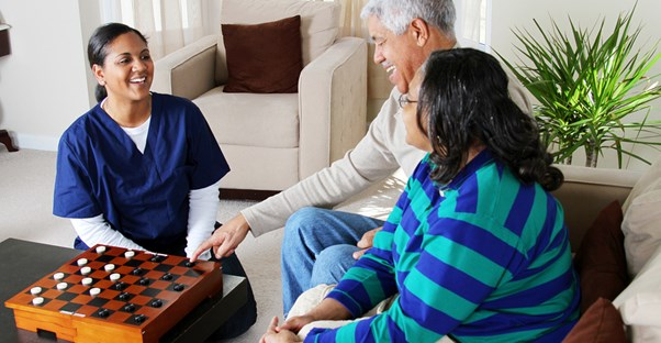 An elderly man and his daughter speak to a representative from a potential senior living community.