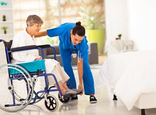 An elderly woman being assisted at a senior care center.