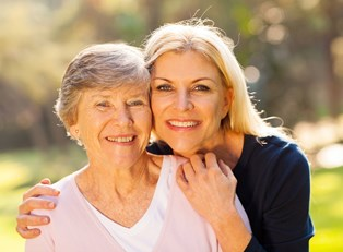 Woman and her ill mother smile, enjoying the time they spend together with at home care