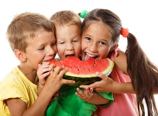 Three kids excitedly eat watermelon after learning about healthy snacks.
