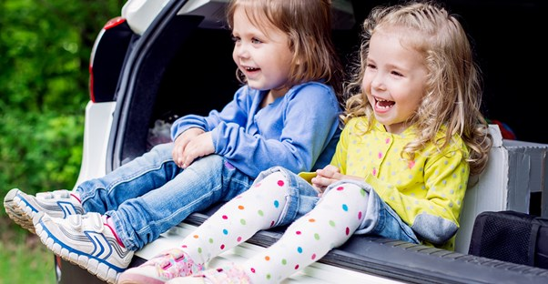 Two little girls smile when they hear the healthy snacks they will eat on a road trip