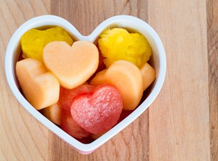 A heart shaped bowl full of fruit given to a kid as a snack.