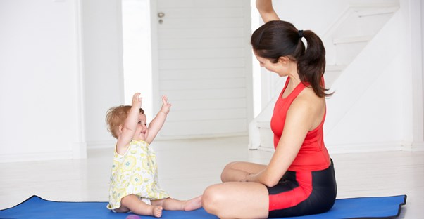 A mom exercising with baby watching