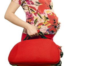 Pregnant woman taking her newly packed hospital bag to the car