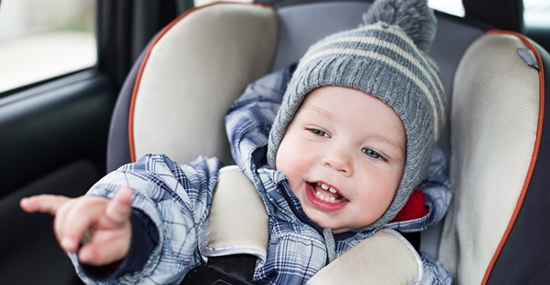 Little boy smiling because he was switched to a forward facing car seat