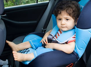 A baby boy sitting in the safest car seat available