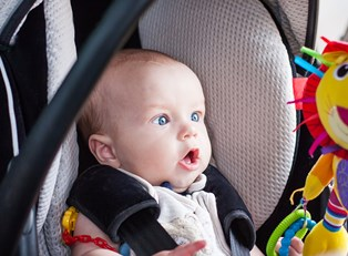 A baby riding in a safe and affordable car seat