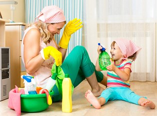 A mom cleaning up a mess made by her daughter.
