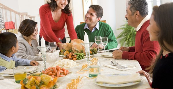 A woman smiling at her in-laws over a holiday dinner.