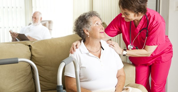 A nurse checking on an elderly woman.