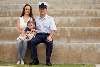 Man in military uniform sitting with wife and baby