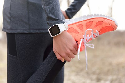 A woman runs with a fitness watch