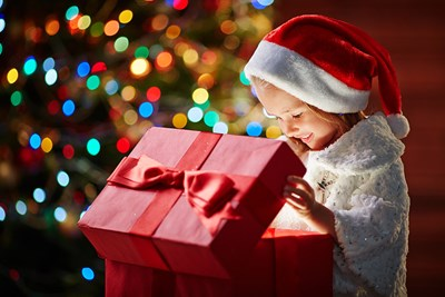 A young girl opens a Christmas gift and the light from the box shines on her face.
