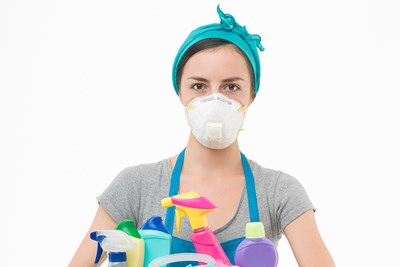 A woman holding a box of cleaning supplies is ready to deep clean her home.