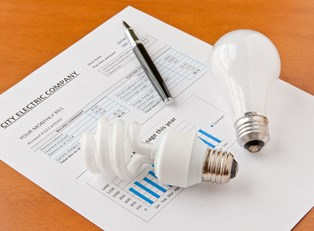 a cfl and incadescent light bulb lying on an electricity bill