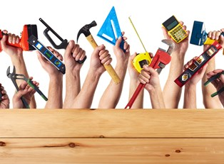 Hands holding tools for DIY home remodeling